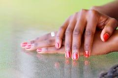 Händer på en tabell med rött spikar polermedel royaltyfri foto