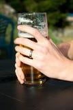 Händer på exponeringsglaset av öl Royaltyfri Foto