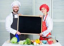 H?nder p? matlagninggrupp Par av mannen och kvinnan som rymmer den tomma svart tavla, i att laga mat skola Kock- och kockhj?lpred royaltyfria bilder