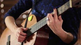 Händer på raderna av en akustisk gitarr Närbild Fokusera skärpaflyttningar från en hand till annan En flicka i en blå klänning är lager videofilmer