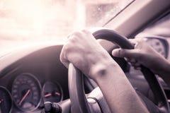 Händer på styrninghjulet av bilkörning Arkivfoto