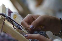 Händer på vertikal gobelängnärbild med den beigea tråden arkivfoton