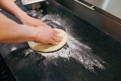 Händer piskar degen, medan forma den Pizzamatlagningprocess Royaltyfri Fotografi