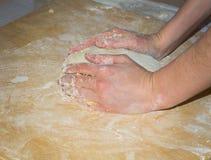 Händer rullar en boll av deg för pizza på hemlagat träbräde med mjöl Arkivfoto