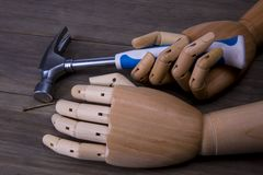 Händer rymmer en hammare och spikar Fotografering för Bildbyråer