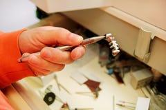 Händer rymmer en tand- krona för stålmetall Royaltyfri Fotografi
