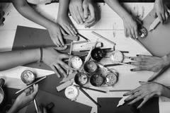 Händer rymmer färgrika markörer, blyertspennor och målarfärger Konsttillförsel i stora och mycket små händer på vit bakgrund Fotografering för Bildbyråer