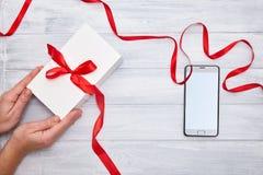 Händer rymmer gåvaasken med det röda bandet och smartphonen på en woodembakgrund royaltyfri fotografi