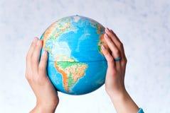 Händer rymmer jordklotet Arkivbild