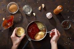 Händer satte senap i kastrullen för att laga mat bbq-sås Royaltyfri Bild
