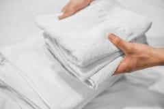 Händer satte vita handdukar på en vit säng Hotellaff?r fotografering för bildbyråer