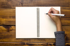 Händer skriver i en anteckningsbok på trägolv Arkivbild