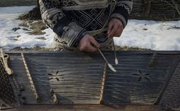 Händer smutsar ner den gamla gatamusikern spelade på ett gammalt musikinstrument royaltyfri foto