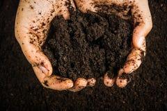 Händer smutsar ner med lera, jordbakgrund Royaltyfri Fotografi