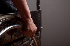 Händer som är höga i rullstol Arkivfoto