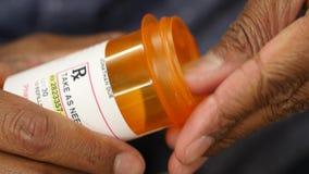 Händer som öppnar en receptpillerflaska arkivfilmer