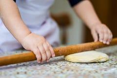 Händer som bakar deg med kavlen på tabellen den lilla kocken bakar i kök Fotografering för Bildbyråer