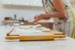 Händer som bakar deg med kavlen på trätabellen Arkivbild