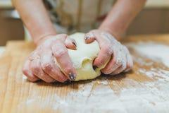 Händer som bakar deg på trätabellen Arkivbild