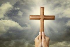 Händer som ber med ett kors arkivbild