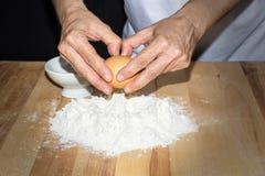 Händer som bryter ett ägg på mjöl royaltyfri fotografi