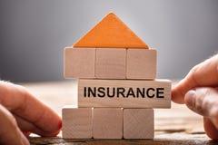 Händer som bygger husmodellen With Insurance Block arkivbilder