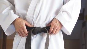 Händer som drar åt det svarta bältet på den iklädda kimonot för man lager videofilmer