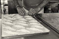 Händer som förbereder den franska gifflet i svartvitt Royaltyfri Foto