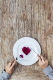 Händer som förbereder sig att äta hjärta på plattan Arkivfoto