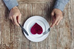 Händer som förbereder sig att äta hjärta på plattan Arkivbilder