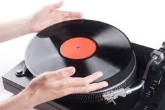 Händer som förlägger LP på skivtallrik Arkivbilder