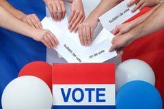 Händer som förlägger slutna omröstningar in i asken med den franska flaggan i bakgrund royaltyfri bild