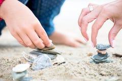 Händer som förlägger stenar på stenpyramiderna på sand Arkivfoto