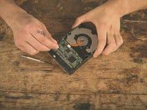 Händer som fixar ett hårt drev på skrivbordet Royaltyfri Bild