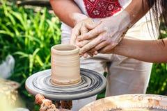 Händer som fungerar på krukmakerihjulet Skulptör keramiker Människahänder som skapar en ny keramisk kruka Arkivbild