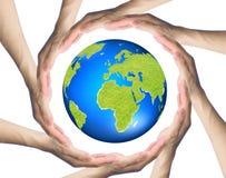 Händer som gör en cirkel som omger jorden arkivfoton