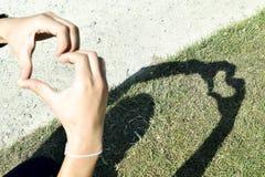Händer som gör hjärtasymbolskugga Arkivfoton