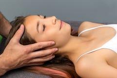 Händer som gör läka fysisk kranie- terapi på barn arkivfoto