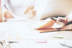 Händer som gör skrivbordsarbete och använder smartphonen Royaltyfri Fotografi