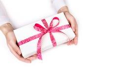 händer som ger gåvaasken med det rosa bandet på vit bakgrund Arkivbilder
