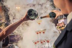 Händer som häller champagne royaltyfri fotografi