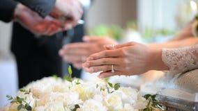 Händer som häller välsignelsevatten in i brudgum och brud, sätter band, thailändskt bröllop