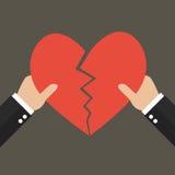 Händer som ifrån varandra river hjärtasymbol Royaltyfri Bild