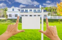 Händer som inramar det tomma Real Estate tecknet och det nya huset arkivbilder