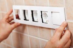 Händer som installerar den dekorativa ramen på elektriska håligheter Royaltyfria Foton