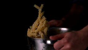 Händer som kastar pasta i durkslag arkivfilmer