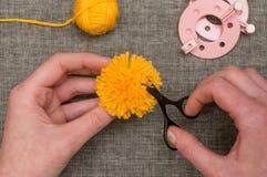 Händer som klipper en gul Pom-pom med trådsax royaltyfri fotografi