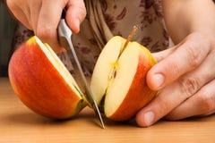 Händer som klipper ett äpple arkivbild