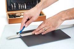 Händer som klipper ett skum, stiger ombord med den skarpa kniven Arkivbild