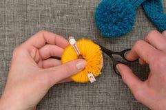 Händer som klipper gult garn som slås in runt om Pom-pomtillverkare royaltyfri bild